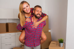 Young couple just move to their new apartment. Boy carrying girl Stock Images