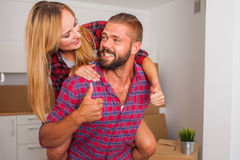 Young couple just move to their new apartment. Boy carrying girl Royalty Free Stock Photos