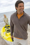 Young couple with kayak on beach Royalty Free Stock Image
