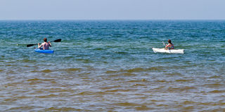Young couple kayaking. Young couple in kayaks off of Lake Michigan shore royalty free stock photography