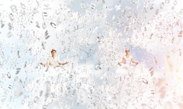 Young couple keeping mind conscious. Young couple keeping eyes closed and looking concentrated while meditating among flying letters in the air with cloudy Stock Image
