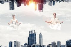 Young couple keeping mind conscious. Young couple keeping eyes closed and looking concentrated while meditating on clouds in the air between two urban worlds Stock Photos