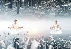 Young couple keeping mind conscious. Young couple keeping eyes closed and looking concentrated while meditating on clouds among flying papers and between two Stock Images