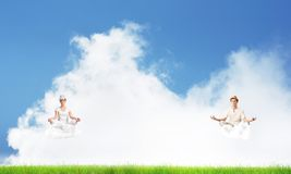 Young couple keeping mind conscious. Young couple keeping eyes closed and looking concentrated while meditating on clouds in the air with bright and beautiful Royalty Free Stock Photo