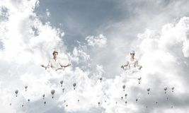 Young couple keeping mind conscious. Young couple keeping eyes closed and looking concentrated while meditating among flying aerostats in the air with cloudy Royalty Free Stock Images