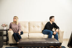 Young couple keeping some distance. Wide view of a young couple sitting on opposite sides of a couch, after having a fight and some problems royalty free stock images