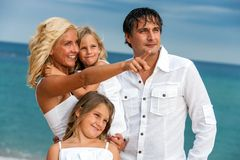 Young couple with kids on beach. Royalty Free Stock Images