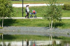Young couple with kids stroller walking in Butovo park, Moscow, Russia royalty free stock photo
