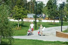 Young couple with kids stroller walking in Butovo park, Moscow, Russia royalty free stock image