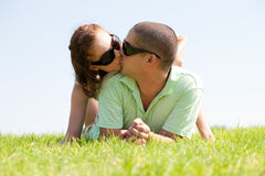 Young Couple kiss. Beautiful young Couple lie down on grass and kiss royalty free stock photos