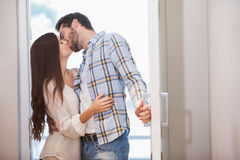 Young couple kiss as they open front door Stock Images