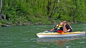 Young Couple Kiss While Kayaking. This sweet photo of romance shows a young Caucasian couple giving a kiss while on a mountain river kayaking Stock Images