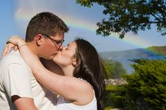 Young Couple kiss by a rainbow. A young couple kiss by the water with a rainbow in the background royalty free stock image