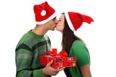 Young couple kiss in Santa hats isolated on white Royalty Free Stock Photography