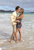Young couple kisses in the waves Royalty Free Stock Photos