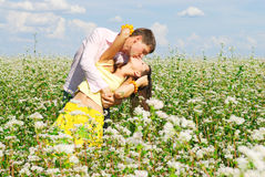 Young couple kissing. Young couple in love who kissing at the meadow Stock Photography