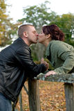 Young Couple Kissing. A young happy couple passionately kissing each other outdoors in the fall Royalty Free Stock Image