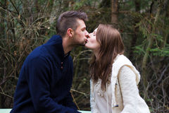 Young couple kissing. In the forest in front of trees Stock Images