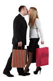 Young couple kissing. Young couple holding shopping bags and kissing against a white background Stock Photography