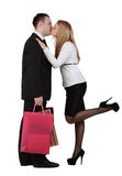 Young couple kissing. Young couple with shopping bags kissing against a white background Stock Photo