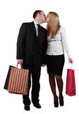 Young couple kissing. Young couple holding shopping bags and kissing against a white background Royalty Free Stock Photography