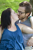 Young couple kissing. A young attractive couple kisses in the park royalty free stock images