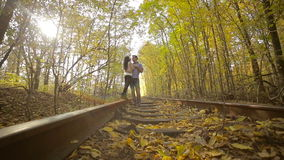 Young couple kissing in autumn park. Lovers standing on an old railway track. Dolly shot stock video footage