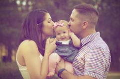Young couple kissing baby girl  Royalty Free Stock Photo