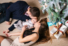 Young couple kissing baby son while lying down on floor Royalty Free Stock Photography