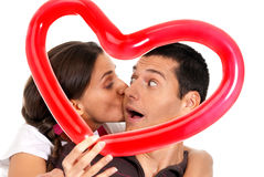 Young couple kissing balloon heart surprise. Young couple kissing through balloon heart surprise on white background royalty free stock photo