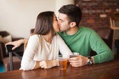 Young couple kissing at a bar Royalty Free Stock Photo