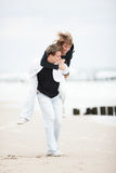 Young couple kissing on beach. With love piggyback Royalty Free Stock Images