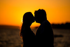 Young couple kissing on the beach sunset Stock Images