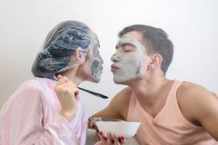 Young couple kissing and beauty mask clay making wellness at home. Spa day, skincare stock images