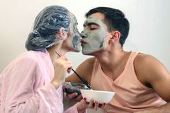 Young couple kissing and beauty mask clay making wellness at home. Spa day, skincare stock photo