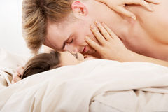 Young couple kissing on bed. Stock Photo