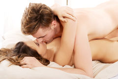 Young couple kissing on bed. Royalty Free Stock Photos