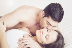 Young couple kissing in bed Royalty Free Stock Photography