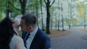Young couple kissing behind big leaves in autumn stock video