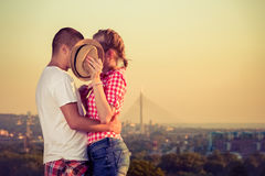 Shy kiss behind hat on first date. Young couple kissing behind hat on first date outdoors. Love concept Royalty Free Stock Photography