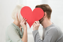 Young Couple Kissing Behind Heart Shape Royalty Free Stock Photos