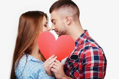 Young couple is kissing behind red heart Stock Photo