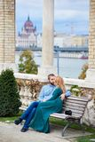 Young couple kissing on bench near the columns of Budapest. Young couple kissing on a bench near the columns on a blurred background of Budapest architecture royalty free stock photography