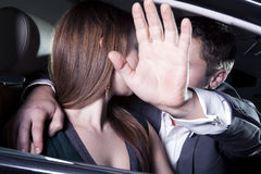 Young couple kissing in car at a red carpet event, man is shielding with his arm outstretched blocking paparazzi photographers. Young couple kissing in car at a royalty free stock photos