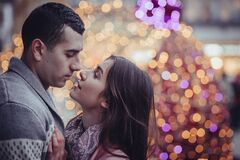 Young Couple Kissing in City at Night Stock Photo