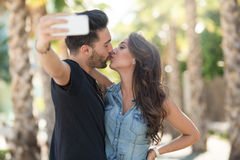 Young Couple Kissing Each Other Posing To Selfie Portrait Of