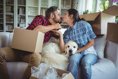 Young couple kissing each other while unpacking carton boxes stock image