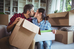 Young couple kissing each other while unpacking carton boxes Stock Photography