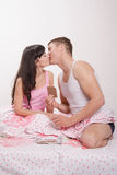 Young couple kissing and eat chocolate in bed Stock Photography
