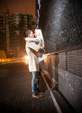 Young couple kissing at evening near black wall Stock Images